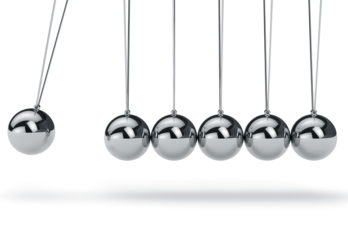 Newtons cradle with metal balls hanging in a line